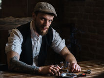 A young bearded man smoking a cigar in a pub Stock Photo