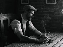 A young bearded man smoking a cigar in a pub Royalty Free Stock Photos