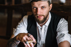 A young bearded man smoking a cigar in a pub Royalty Free Stock Images