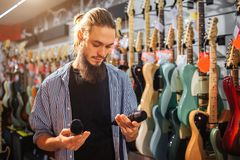Young bearded man stand close to electric guitars in room. He hold two black microphones in hands. Guy look at them. He. Is concentrated royalty free stock images