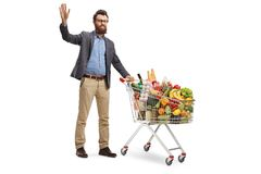 Young bearded man standing with a shopping cart and waving. Full length portrait of a young bearded man standing with a shopping cart and waving isolated on stock photo