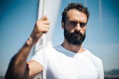 Young bearded man standing on a yacht and looking Stock Photo