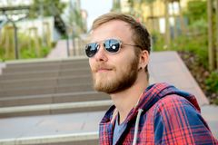 Young bearded man with sunglasses standing on stairs. Young bearded man with sunglasses in checkered shirt standing on stairs Stock Photo