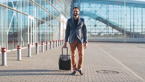 Young bearded man in sunglasses having a business trip, pulling the suitcase to the airport. Active lifestyle, having stock video