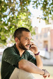 Young bearded man talking over phone Royalty Free Stock Images