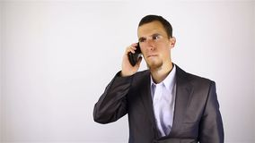 Young bearded man talking on the phone. bad news. Grey background stock video footage
