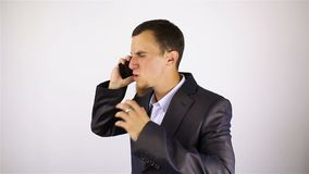 Young bearded man talking on the phone. bad news. Grey background stock footage