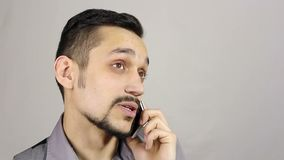Young bearded man talking on the phone stock video