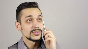 Young bearded man talking on the phone stock video footage