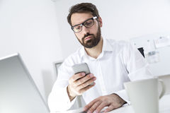 Young bearded man texting at work Royalty Free Stock Image