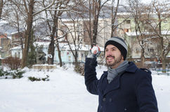 Young bearded man throwing a snowball Stock Photo