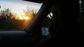 Young bearded man traveling in the car looking outside the window at sunset stock video