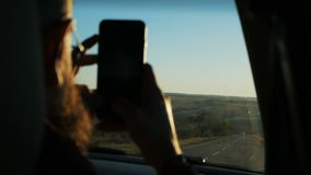 Young bearded man traveling in the car looking outside the window at sunset stock video footage