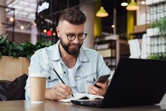Young bearded man trendy glasses sits cafe in front of laptop computer, uses smartphone, takes notes in notebook. Young bearded hipster man trendy glasses sits stock photography