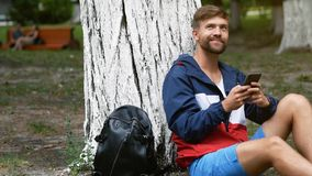 Young bearded man typing a message by mobile phone sitting under the tree. Student chatting in the park stock video