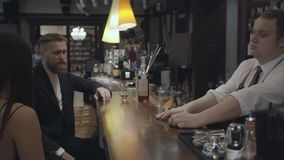 The young bearded man and unrecognizable brunette woman sitting at the bar counter. Plump bartender mixing alcohol in. The glass before to give it to client stock footage