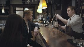 The young bearded man and unrecognizable brunette woman sitting at the bar counter. Plump bartender pouring alcohol in. The glass using measuring cup and giving stock video footage