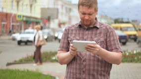 A young bearded man uses a digital tablet next to a busy road stock video