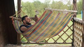 A young bearded man uses a tablet, communicates using video conferencing, lying in a hammock in a country house.  stock video footage