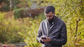 Young bearded man using phone in sunny park stock footage