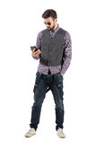 Young bearded man using smartphone with other hand in pocket Royalty Free Stock Images