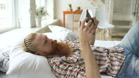 Young bearded man using tablet computer lying on bed in bedroom at home. Young bearded man using tablet computer lying on the bed and surfing internet in bedroom stock video