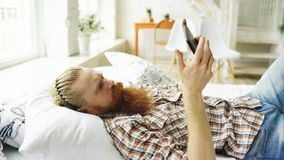 Young bearded man using tablet computer lying on bed in bedroom at home. Young bearded man using tablet computer lying on the bed and surfing internet in bedroom Stock Photo