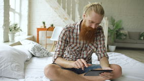 Young bearded man using tablet computer sitting on bed in bedroom at home. Young bearded man using tablet computer sitting on the bed and surfing internet in stock footage