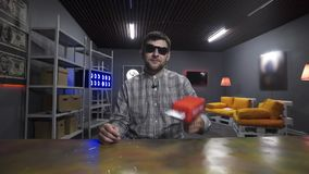 Young bearded man vlogger shoots with dollar banknotes from red plastic gun. Cute young bearded male vlogger wearing sunglasses and checkered shirt, speaks and stock video