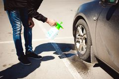 Portrait of a man with a beard with a mustache. Young bearded man washes his car`s wheel rims, spraying water from spray, in street parking Royalty Free Stock Photos
