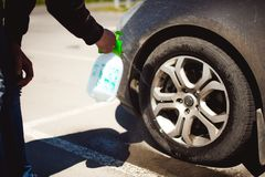 Young bearded man washes his car`s wheel rims, spraying water from spray Stock Photography