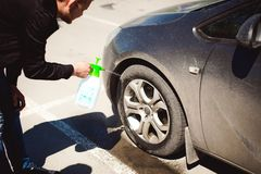 Young bearded man washes his car`s wheel rims, spraying water from spray Stock Image