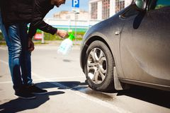 Young bearded man washes his car`s wheel rims, spraying water from spray Royalty Free Stock Images