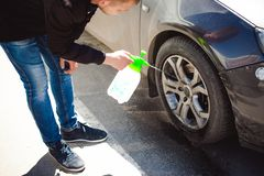 Young bearded man washes his car`s wheel rims, spraying water from spray Stock Photos