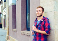 Young bearded man with water bottle in checkered shirt Stock Photo