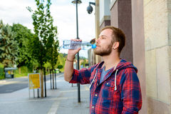 Young bearded man with water bottle in checkered shirt Royalty Free Stock Image