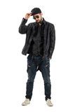 Young bearded man wearing baseball cap, sunglasses in leather jacket. Full body length portrait isolated over white background Royalty Free Stock Images