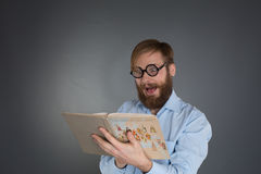 Young bearded man wearing glasses reading a book Royalty Free Stock Image