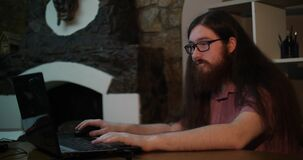 Young bearded man wearing glasses working with laptop in dark office late at night, his face lit up by screen stock video footage