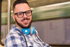 Man wearing plaid shirt and glasses taking public transport underground area. Concept of commute, mobility, city life. royalty free stock photos