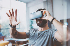 Young bearded man wearing virtual reality glasses in modern interior design coworking studio. Smartphone using with VR. Goggles headset. Horizontal,flares stock photography