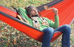 Young bearded man with wistful smile and a guitar relax in a ham Royalty Free Stock Photo