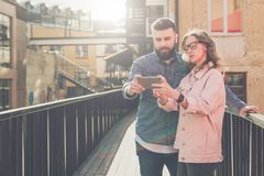 Young bearded man and woman stand outside and discuss what they see on smartphone screen. Girl shows the guy information stock photos