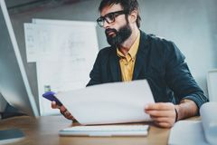 Young bearded man working at sunny while sitting at wooden table.Designer analyze new ideas on modern computer.Blurred. Background,horizontal Stock Images