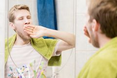 Young bearded man yawn in front of mirror in the bathroom stock images