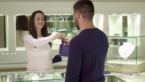 Man buys jewelry at the boutique. Young bearded men buying jewelry at the boutique. Pretty female seller putting purchase in little bag and give it to the client Royalty Free Stock Images