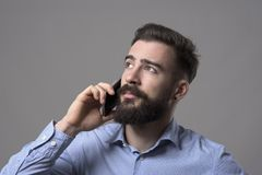 Young bearded modern smart casual business man talking on the phone looking up at copyspace. Against gray studio background Stock Image