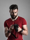Young bearded photographer reviewing photos on rear lcd screen of dslr camera Stock Photography