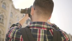 Young bearded photographer taking a photo in the street of an old city with beautiful architecture. Tourist takes. Young newbie bearded photographer taking a stock video