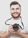 Young bearded photographer taking pictures with digital camera. Royalty Free Stock Image